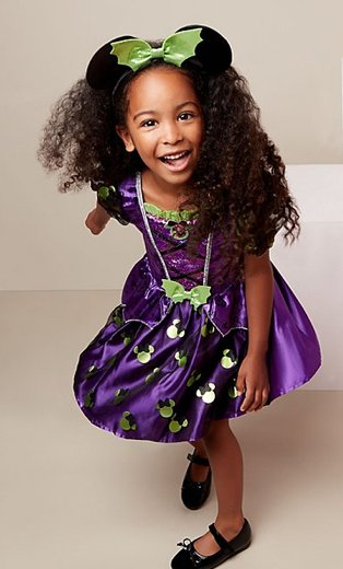 Girl poses wearing Disney Minnie Mouse purple witch fancy dress costume with white boxes in the background