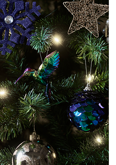 Christmas tree branches decorated with purple and gold decorations
